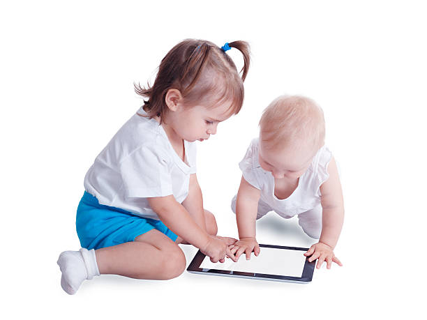 Two little kids playing with tablet computer stock photo