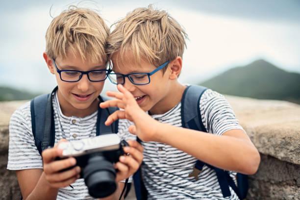 due piccoli fotografi che si godono una nuova macchina fotografica. - gemelle foto e immagini stock