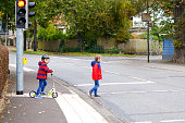 Two little schoolkids boys running and driving on scooter on autumn day. Happy children in colorful clothes and city traffic crossing pedestrian crosswalk with traffic lights