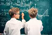 Two little scientists discussing science problems at the blackboard. There are some complicated equations and formulas on the blackboard.\nNikon D850