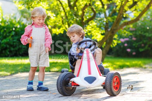 915609494istockphoto Two little sibling boys playing with pedal car in garden 510391873