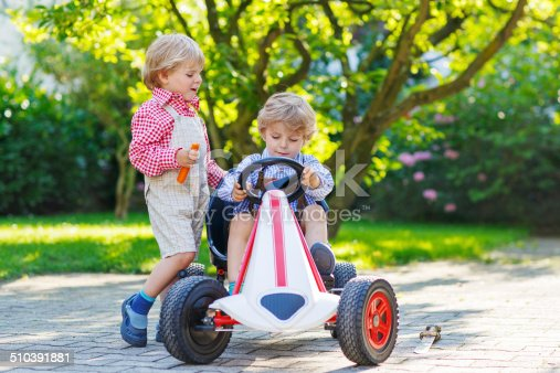 915609494istockphoto Two little sibling boys playing with pedal car in garden 510391881