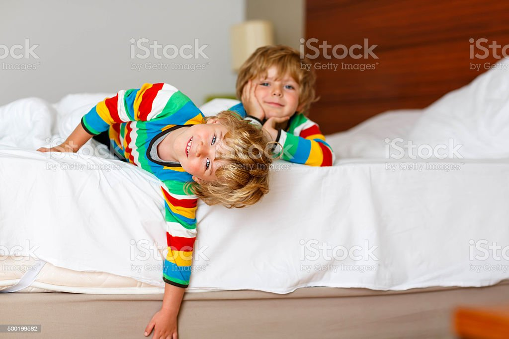 Two little sibling kid boys having fun in bed stock photo