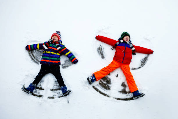 Two little siblings kid boys in colorful winter clothes making snow angel, laying down on snow. Active outdoors leisure with children in winter. Happy brothers with warm hat, gloves, winter fashion. stock photo