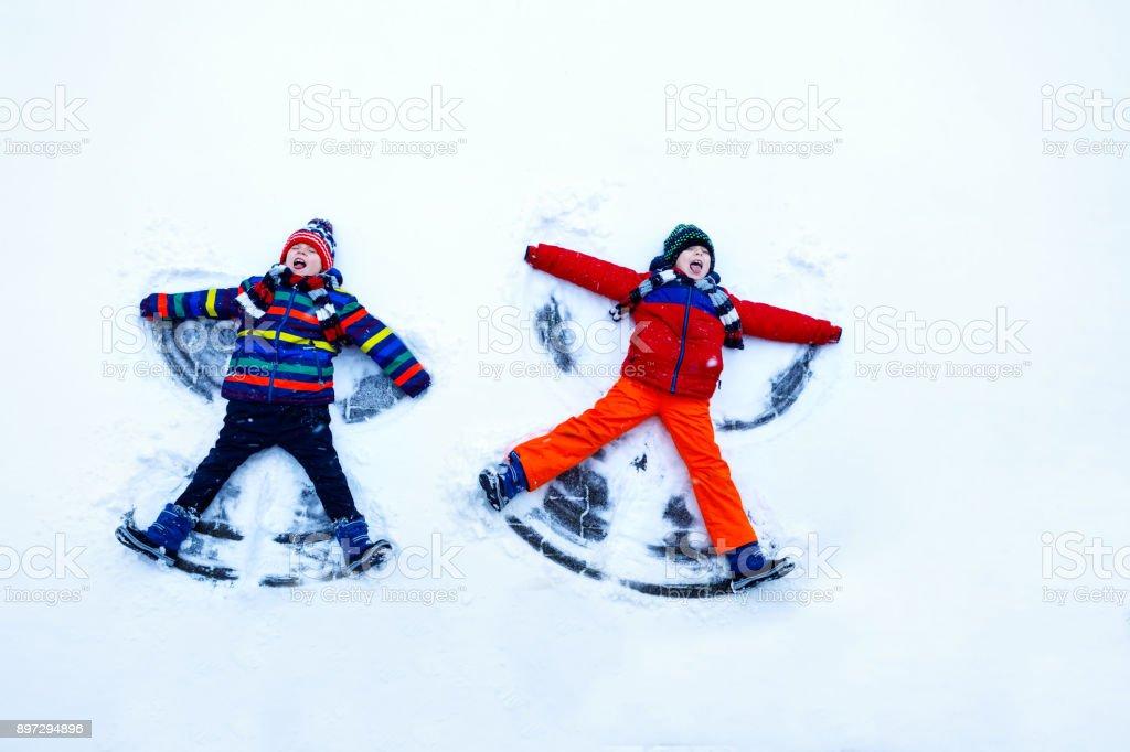 Zwei kleine Geschwister Kind jungen in bunten Winterkleidung machen Schnee-Engel, Festlegung auf Schnee. – Foto