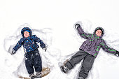 Two little siblings kid boys in colorful winter clothes making snow angel, laying down on snow. Active outdoors leisure with children in winter. Happy brothers