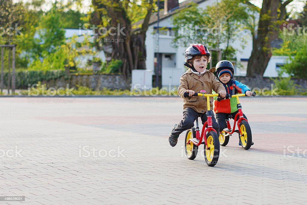Two little siblings riding bikes in city on vacations stock photo