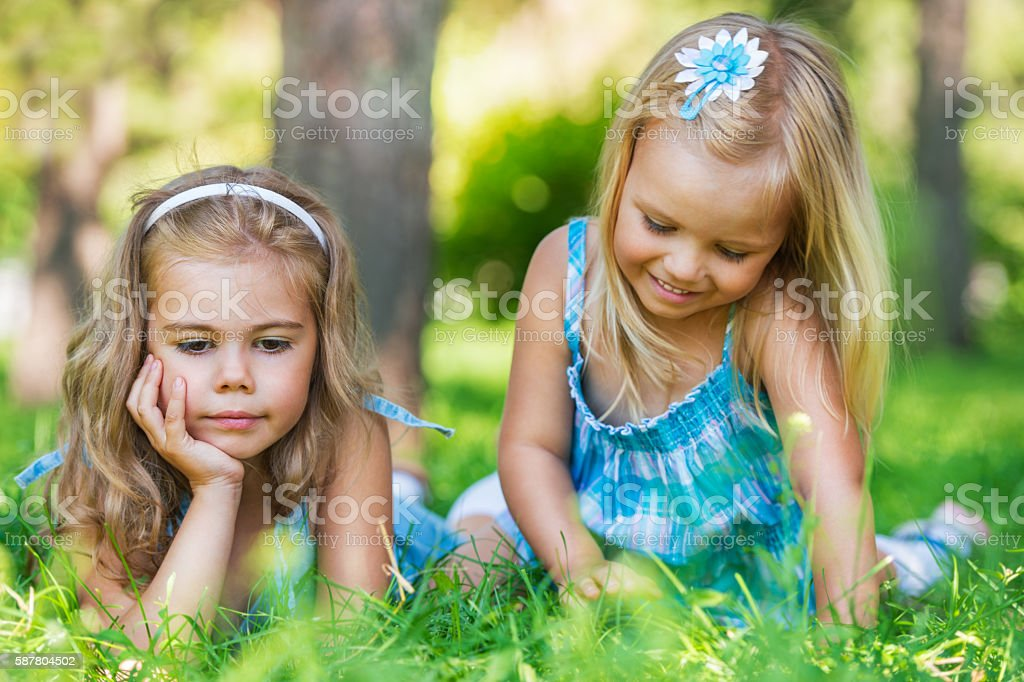 Two little sisters having fun in summer park stock photo