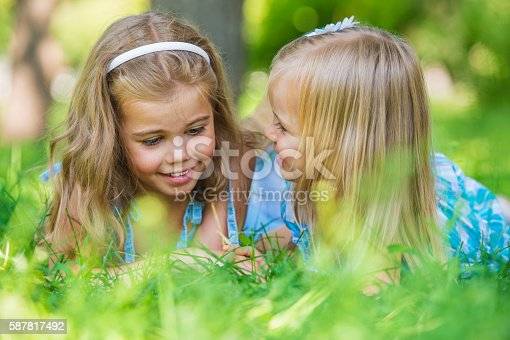 Two little sisters having fun in summer park while lying on lawn