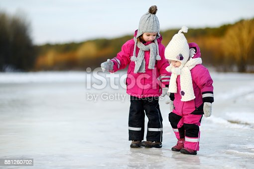 istock Two little sisters having fun on snowy winter day 881260702