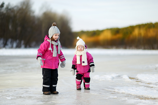 Two little sisters having fun on snowy winter day