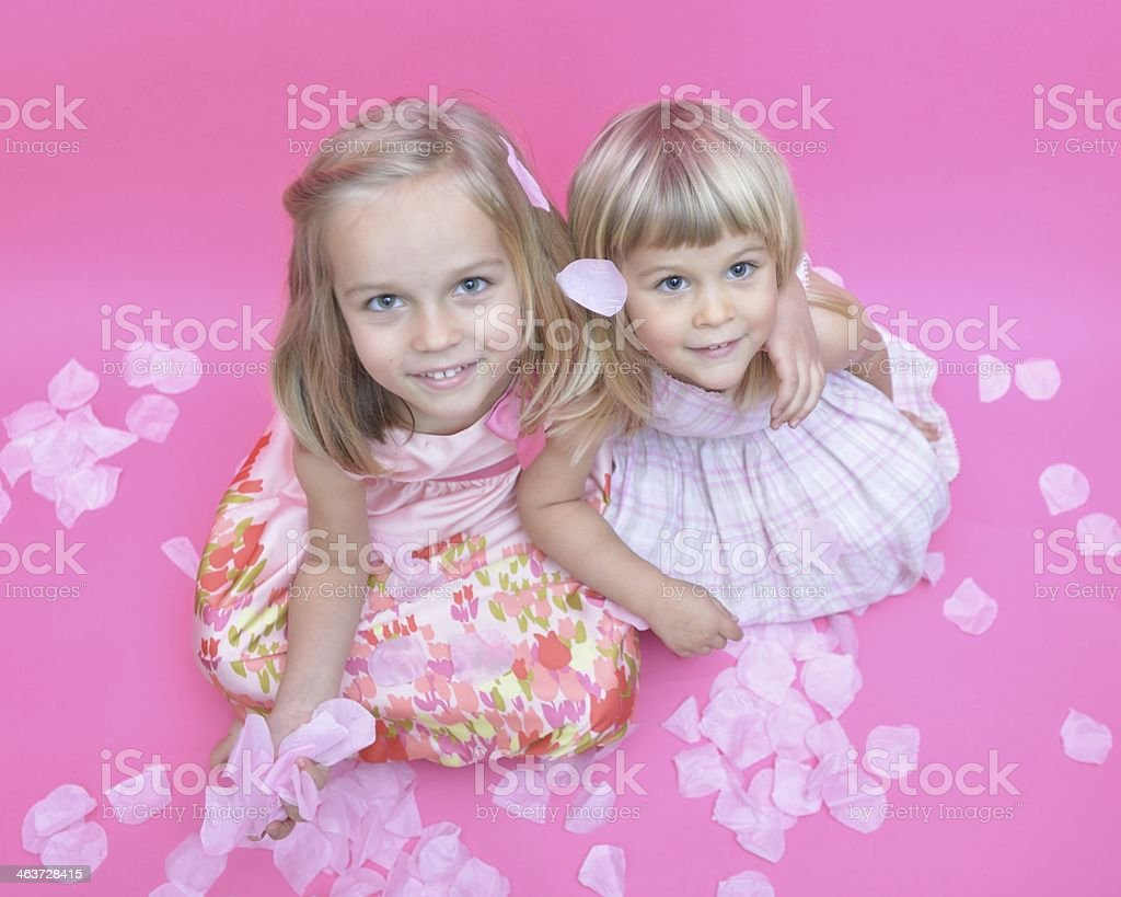 Two little sisters in rose petals stock photo