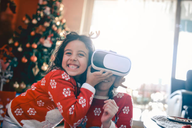 zwei kleine schwestern spielen und kämpfen über virtual-reality-simulator - kinder weihnachtsfilme stock-fotos und bilder