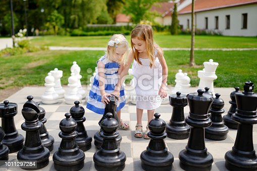 Two little sisters playing giant chess outdoors