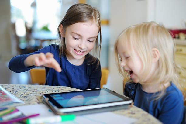 Zwei kleine Schwestern spielen mit einem Digitaltablett – Foto