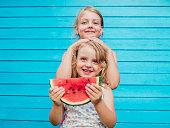 Two little sisters together with red ripe watermelon smiling. Over blue plank wall background