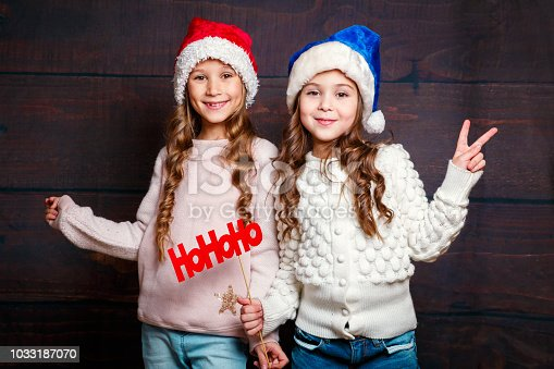 1062609644 istock photo Two little smiling girls having fun .Christmas concept. Smiling funny sisters in Santa hat on wooden background 1033187070