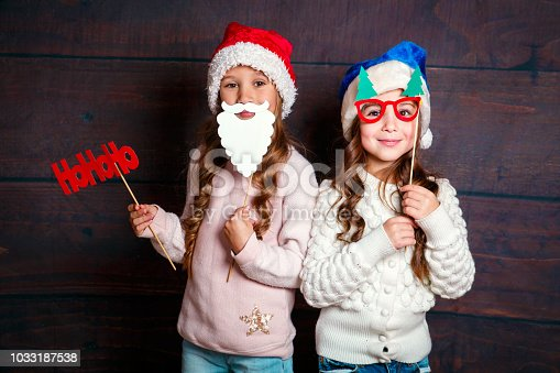 1062609644 istock photo Two little smiling girls having fun .Christmas concept. Smiling funny sisters in Santa hat on wooden background 1033187538