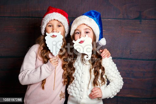 1062609644 istock photo Two little smiling girls having fun .Christmas concept. Smiling funny sisters in Santa hat on wooden background 1033197288