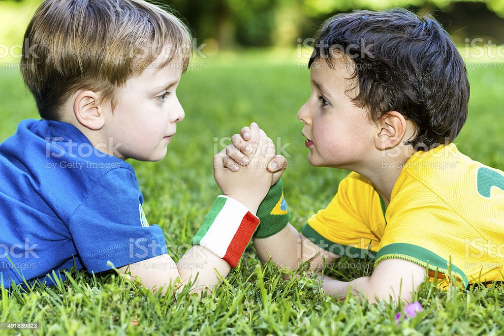 Two little soccer fans doing arm wrestling royalty-free stock photo