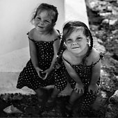 Two little identical twin toddler girls looking up in the summer outside