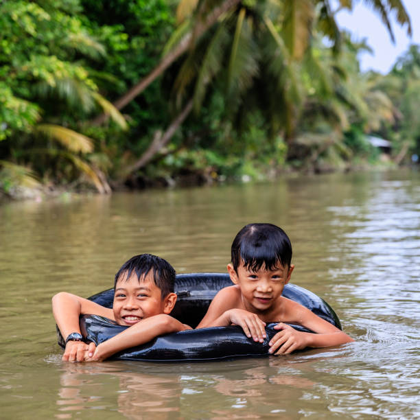 two little vietnamese boys bathing in mekong river delta, vietnam - mekong river stock pictures, royalty-free photos & images