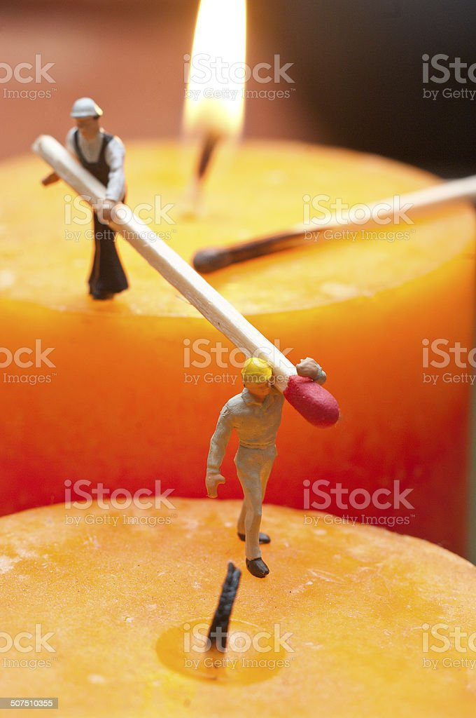 Two little workers lit candles. The concept of teamwork stock photo