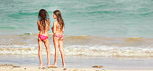 A DSLR Canon photo of two brazilian girls in bikini by the sea with their backs to the camera. They are in Toque Beach in Porto dos Milagres, Alagoas, Northeastern Brazil. It is a bright sunny summer day.