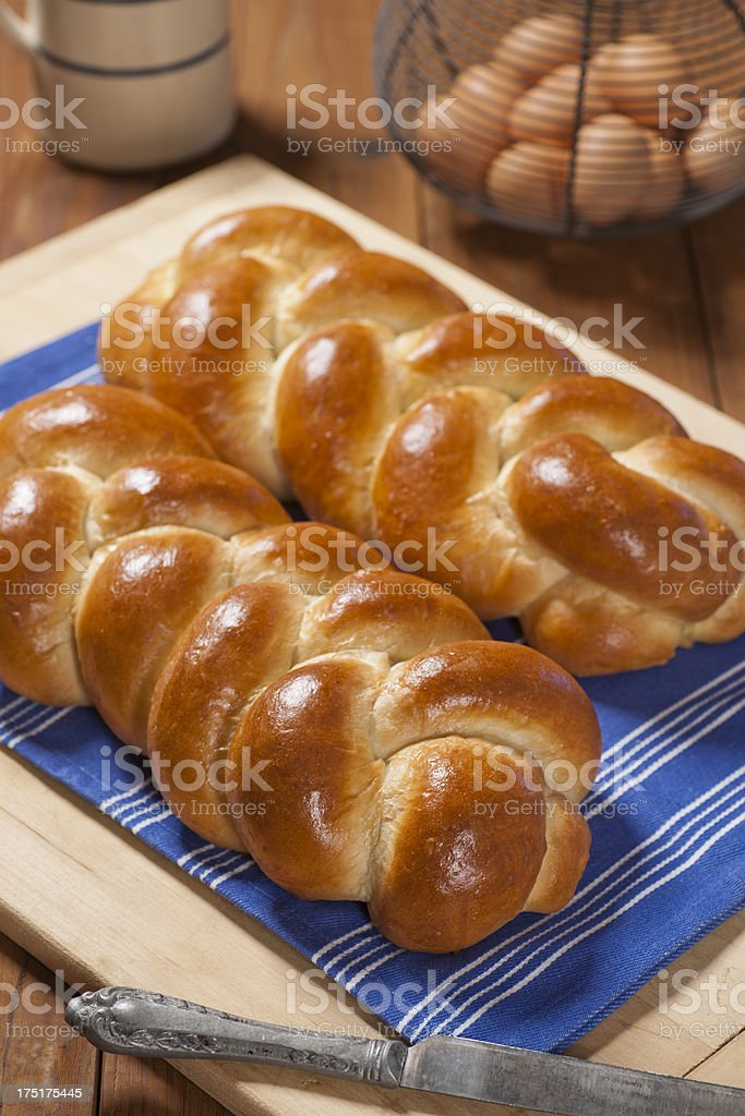 Two loaves of challah bread on a blue dinner napkin stock photo