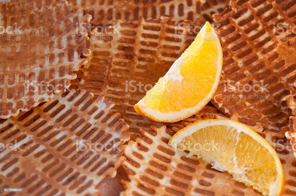 Two lobules orange on a background of crispy waffles stock photo