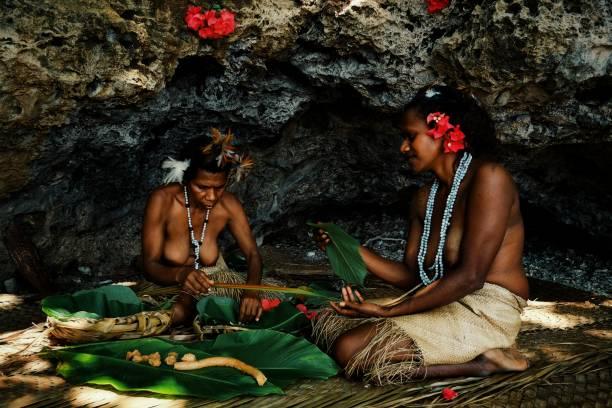 zwei lokale indianerin, die traditionelle laplap kochen an der tropischen küste in bambus und bananen blatt - kochinsel stock-fotos und bilder