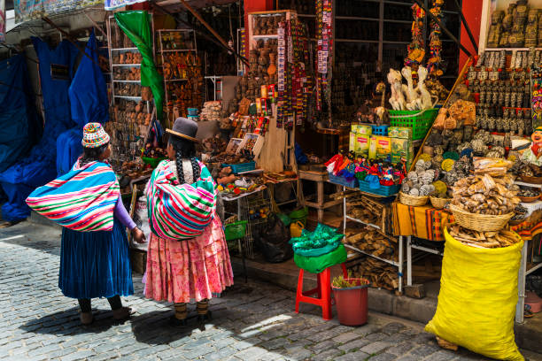 Two local woman wearing traditional clothing in front of a store in a street of the city of La Paz, in Bolivia stock photo