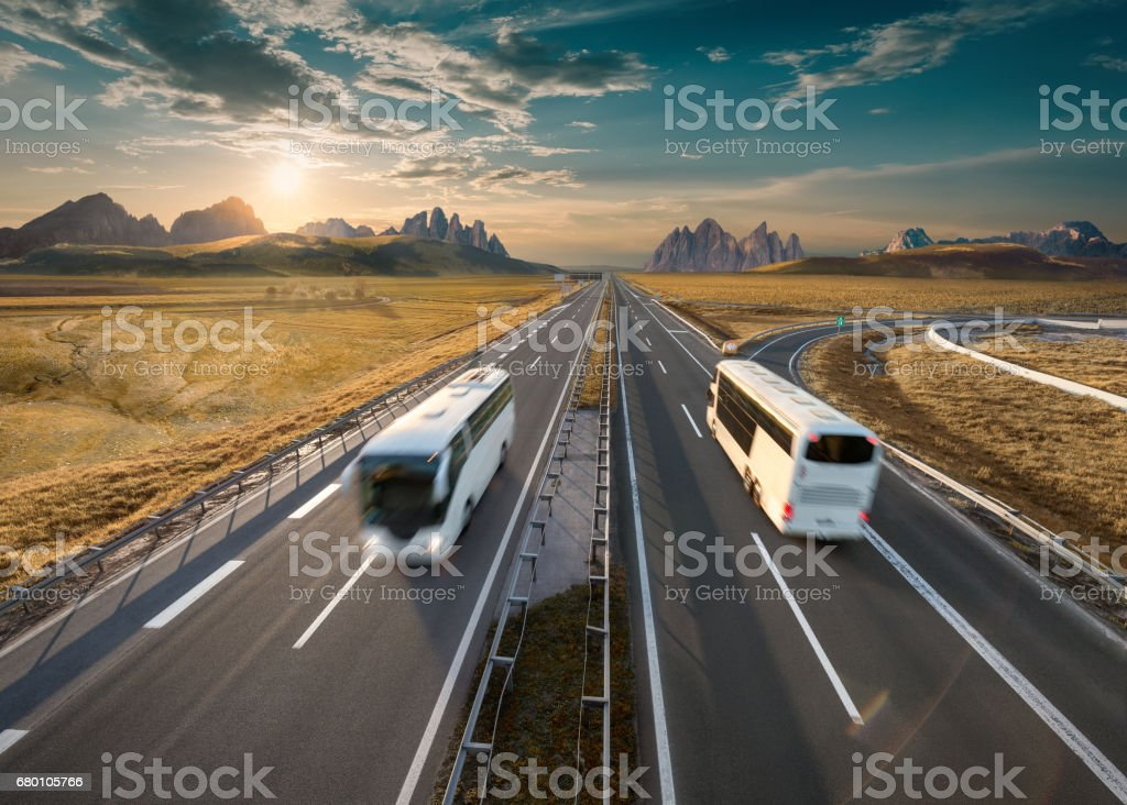 Two lone buses on highway at idyllic sunny morning - foto de stock