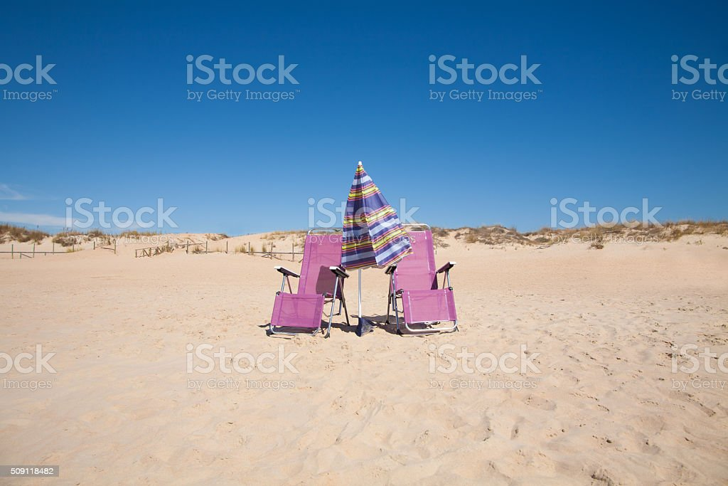 two lonely chairs and umbrella at beach stock photo
