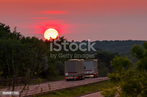Three lane motorway at sunset with two lorries heading west