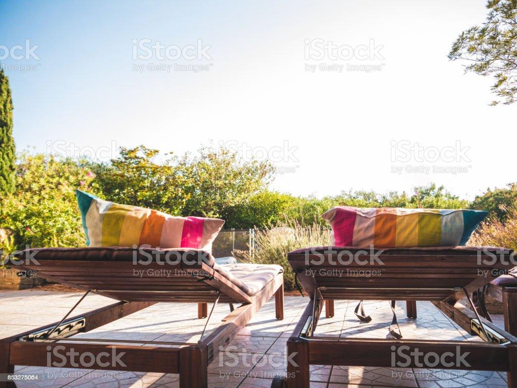 Zwei Liegestühle am Pool mit blauem Himmel – Foto