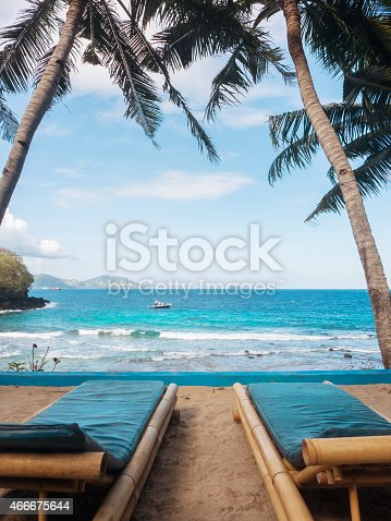 istock Two loungers on a tropical beach in front of water 466675644