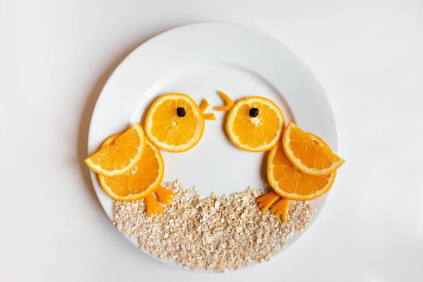 Dos pájaros de amor hechos de naranja servidos en un plato blanco - foto de stock