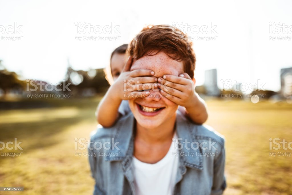 two lovely kids piggyback at the park stock photo
