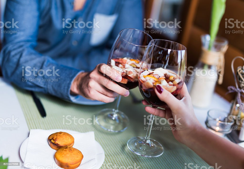 Two lovers cheering with sangria in a restaurant stock photo
