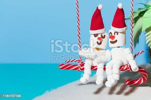 istock Two lovers of Marshmallow snowmen are sitting on a swing of candy. Christmas holidays on the beach. 1184707155