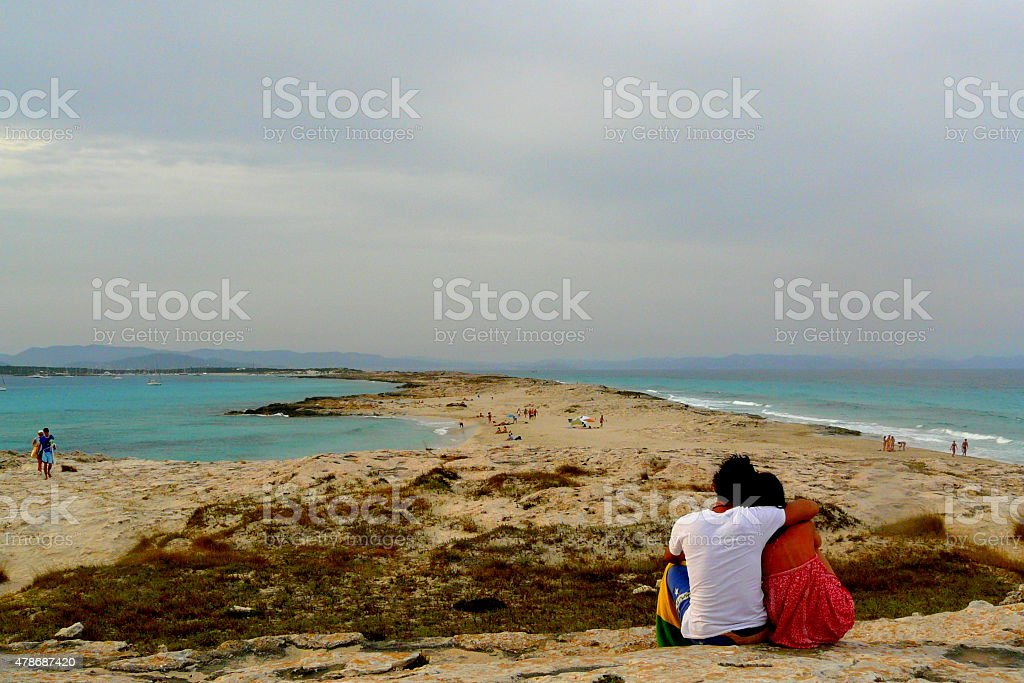 Two lovers sitting together in Ses Illetes beach, Formentera stock photo