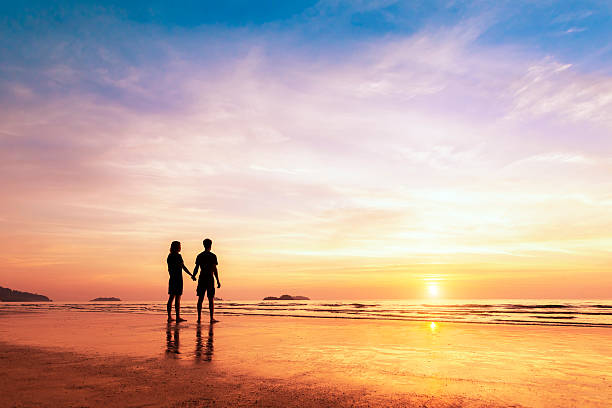 Two lovers standing together on a beach thinking about life stock photo