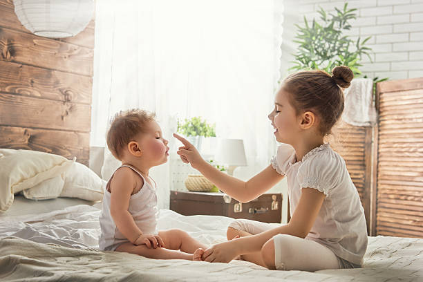 two loving sisters two cute child baby girls playing and having fun on the bed. loving sisters hug sibling stock pictures, royalty-free photos & images