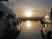Two luxury yachts docked at the port of Saint-Tropez during a beautiful sunset.