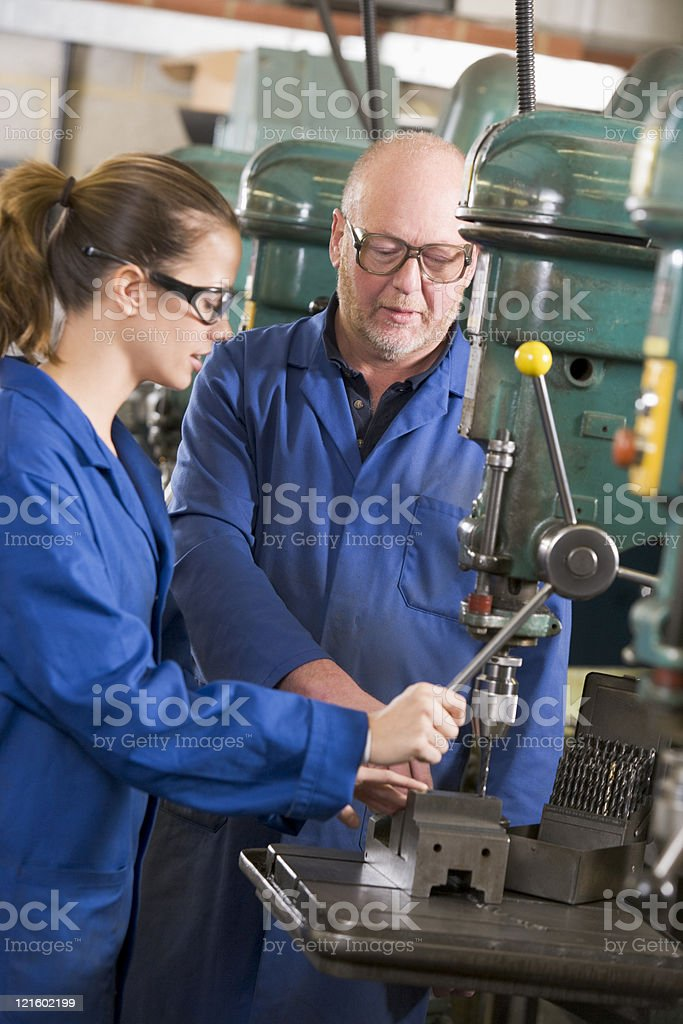 Two machinists working on machine royalty-free stock photo