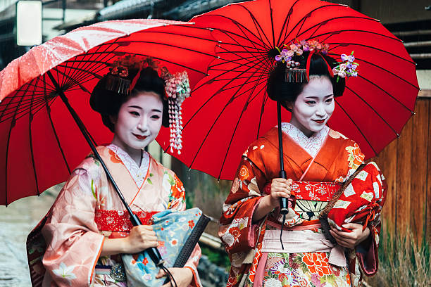 two maiko geisha walking on a street in kyoto, japan - geisha girl stock photos and pictures