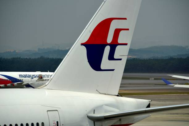 Two Malaysia Airlines aircraft cross at Kuala Lumpur International Airport (KLIA), Malaysia Kuala Lumpur, Malaysia: two Malaysia Airlines jets taxiing at Kuala Lumpur International Airport (KLIA) - forest and hills in the background, Sepang, Selangor kuala lumpur airport stock pictures, royalty-free photos & images