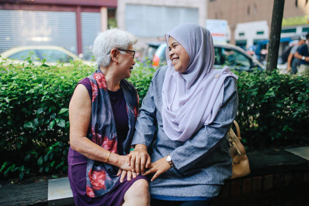 Two Malaysian women talking on the street of Kuala Lumpur stock photo