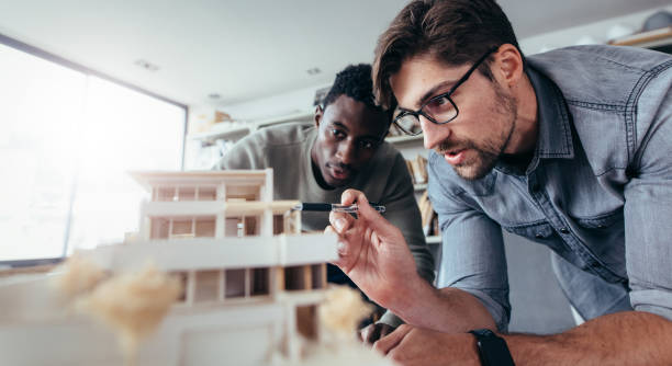 zwei männliche architekten diskutieren über hausmodell - architekturberuf stock-fotos und bilder